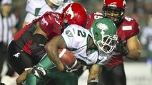 Saskatchewan Roughriders running back Jock Sanders is tackled by Calgary Stampeders defensive lineman Junior Turner and linebacker Karl McCartney in the forth quarter of CFL preseason football action in Regina, Sask., Thursday, June 20, 2013. (Liam Richards/THE CANADIAN PRESS)