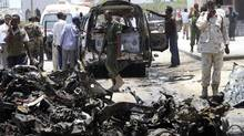 A Somali soldier uses his mobile phone to record the wreckage of vehicles at the scene of an explosion near the presidential palace in Somalia's capital Mogadishu March 18, 2013. (Omar Faruk/Reuters)