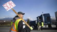 Many logging companies are considering moving logs through the Port of Prince Rupert during the strike. Christopher Sequeira, a truck driver for 10 years, holds up a scab sign as non-unionized trucker drives pass an information picket line outside the Port Metro Vancouver, March 11, 2014. (John Lehmann/The Globe and Mail)