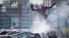 A stuntman dressed as Marvel Comics character Deadpool leaps from a vehicle during filming of the movie, shot in Vancouver in 2015. (DARRYL DYCK For The Globe and Mail)