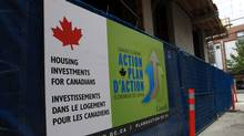 A Government of Canada economic action plan sign hangs on a fence at a social housing project under construction at Abbott St. and West Pender St. in Vancouver, B.C., on May 24, 2010. (DARRYL DYCK)