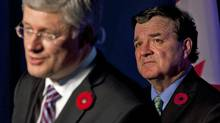 Finance Minister Jim Flaherty listens as Prime Minister Stephen Harper gives a news conference at the G20 Summit in Cannes, France, on Nov. 4, 2011. (Adrian Wyld/THE CANADIAN PRESS)