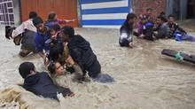 Kashmiri residents wade through floodwaters in Srinagar, India, Sept. 4, 2014. At least 100 villages across the Kashmir valley were flooded by overflowing lakes and rivers. (Dar Yasin/Associated Press)