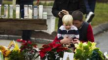A man embraces a young boy as they look at a memorial in front of the St. Rose of Lima Catholic church in Newtown, Conn., Dec. 16, 2012. (LUCAS JACKSON/REUTERS)