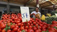 A trader selects tomatoes from a stall with a euro price sign at Athens central market in Athens, Greece, on Tuesday, June 19, 2012. Greek voters are likely to get a reward for backing pro-euro parties, with European creditors set to ease bailout terms on the debt-swamped country mired in the fifth year of recession. (Chris Ratcliffe/Bloomberg)