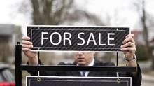 A broker puts up a For Sale sign before an open house in Toronto in this 2015 file photo. (Darren Calabrese For The Globe and Mail)