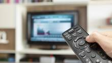 Watching Economy Channel With TV Remote Control In Hand (Omer Yurdakul Gundogdu/Photos.com)