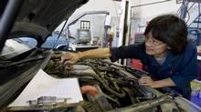 Hong Truong diagnoses a problem in a customer's car in Edmonton. (John Ulan)
