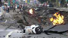 Vehicles are left lying on a destroyed street as part of the street is burning with flame following multiple explosions from an underground gas leak in Kaohsiung, Taiwan, early Friday, Aug. 1, 2014. (AP)