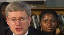 Prime Minister Stephen Harper, left, sits next a girl associated with Pathways to Education Canada, a charitable organization to reducing poverty and providing post-secondary education as they pose for a photo
