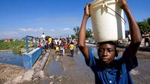 A boy carries a hard won bucket of water away from a broken water pipe in the commune of Cite Soleil in Port-au-Prince, Haiti. (Handout/Logan Abassi/MINUSTAH via Getty Images)
