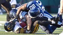 Hamilton Tiger-Cats Deon Murphy (bottom) is tackled by Toronto Argonauts David Lee and Nick Clement (20) in the first half of their CFL pre-season football game in Hamilton June 13, 2012. (FRED THORNHILL/REUTERS)