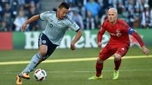 Sporting KC player Roger Espinoza (27) dribbles the ball against Toronto FC player Michael Bradley (4) during the first half on Sunday, March 20, 2016. (Peter Aiken/USA Today Sports)