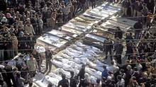 In this citizen journalism image provided by the Local Coordination Committees in Syria, Syrian mourners gather around the coffins of the victims who were killed early Saturday by the bombardment of mortars and rockets during a mass funeral procession, in Khaldiyeh neighborhood in Homs province, central Syria, on Feb. 4, 2012. (AP/AP)