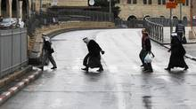 Palestinians cross the street after Friday prayers near Damascus Gate in Jerusalem's Old City Nov. 23, 2012. Israeli security forces declared an age limitation on Friday for Palestinians wanting to enter the Old City, only allowing males above the age of 40 and all females to enter. (AMMAR AWAD/REUTERS)