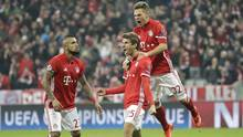 Bayern's Thomas Mueller, center, celebrates with teammates Joshua Kimmich, right, and Arturo Vidal after scoring his side's fifth goal during the Champions League round of 16 match against Arsenal (Matthias Schrader/AP)