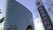 A man walks past the headquarters of the state-owned China National Offshore Oil Corp. (CNOOC) in Beijing, China Saturday, Dec. 8, 2012. (Andy Wong/AP)