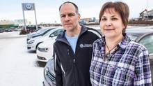 Kevin and Darlene Bathgate stand in front of the Volkswagen dealership sold to AutoCanada. (Chris Beauchamp for The Globe and Mail)