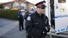 RCMP and Toronto police go in and out of a house in Toronto on April 22, 2013. The house is believed to be the residence of one of two suspects arrested in an alleged plot against a passenger train. (Tim Fraser for The Globe and Mail)