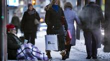 Pedestrians pass a homeless man on Bay Street in downtown Toronto on Dec. 16, 2013. (Peter Power/The Globe and Mail)