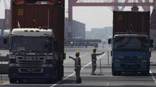 Workers check containers loaded on trucks at a port in Tokyo on July 25, 2012. In Japan, at least part of the drop-off in exports in June can be blamed on the strength of the Japanese yen. (YURIKO NAKAO/REUTERS)
