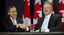 Bank of Canada Governor designate StephenPoloz (right) shakes hands with outgoing Governor Mark Carney during a news conference in Ottawa, on Thursday May 2, 2013. (Adrian Wyld/THE CANADIAN PRESS)