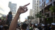 A woman gestures towards the ranks of police officers as a speaker addresses demonstrators gathered outside Toronto Police headquarters. (Chris Young/The Canadian Press)
