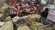 Vendors nap on chairs amongst boxes of fruits at a wholesale fruit and vegetable market in Wuhan, Hubei province July 6, 2012. (DARLEY SHEN/REUTERS)