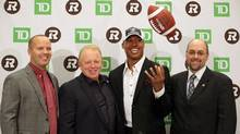 Ottawa Redblacks staff (left to right) head coach Rick Campbell, president Jeff Hunt and general manager Marcel Desjardins introduce free agent quarterback Henry Burris (second from right) at a press conference in Ottawa on Tuesday, February 4, 2014. (Mike Carroccetto/THE CANADIAN PRESS)