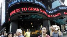 In this Sept. 15, 2008, file photo tourists take pictures in New York's Times Square as the days financial news about the bankruptcy of Lehman Brothers is displayed on the ABC news ticker. (Mary Altaffer/Associated Press)
