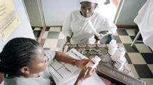 Esther Babalola, 38-year-old mother of four, receives a cocktail of modern AIDS medicines from Tope Olorunkoya, a health technician at the HIV/AIDS clinic in Sagamu, southern Nigeria. (Boris Heger/The Associated Press/Boris Heger/The Associated Press)