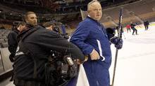 An HBO 24/7 sound crew member turns Toronto Maple Leafs Head Coach Randy Carlyle's microphone on during Leafs practice (Deborah Baic/The Globe and Mail)