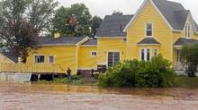 A resident looks on as dikes on the Salmon River gave way in Truro, N.S. on Monday, Sept. 10, 2012. (Andrew Vaughan/The Canadian Press)