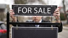 Broker Paul Siksna puts up a For Sale sign before an open house in Toronto on Tuesday, April 7, 2015. (Darren Calabrese For The Globe and Mail)