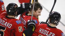 Calgary Flames' Chris Butler, centre, is congratulated by teammates after scoring the winning goal during overtime NHL action in Calgary, Alta., Thursday, Dec. 12, 2013. (Jeff McIntosh/THE CANADIAN PRESS)