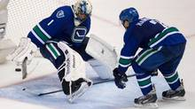 Vancouver Canucks' Dan Hamhuis, right, and goalie Roberto Luongo watch as a Canucks pass bounces off Luongo's skate and into their own net for a Montreal Canadiens goal during the second period of an NHL game in Vancouver, B.C., on Saturday October 12, 2013. (DARRYL DYCK/THE CANADIAN PRESS)
