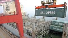 A shipping container is lifted by a crane at a port in Lianyungang, Jiangsu province April 10, 2014. (REUTERS)