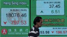 A man walks past a display board showing the Hang Seng stock market index in Hong Kong on October 18, 2011. (LAURENT FIEVET/AFP/Getty Images)
