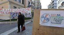 A sign playing on the Greek acronym of dominant electricity producer Public Power Corporation reads 'I can't pay additional taxes and the property levy,' in central Veria, northern Greece, on Friday, Nov. 18, 2011. As two years of pay cuts and tax hikes pummel living standards in debt-crippled Greece, many in this northern town can't pay for basic utilities such as electricity - and get cut off from the grid. (Nikolas Giakoumidis/AP/Nikolas Giakoumidis/AP)