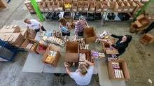 Volunteers sort though boxes of donated food at the Daily Bread Food Bank in Toronto on Sept. 16, 2016. (Glenn Lowson for The Globe and Mail)