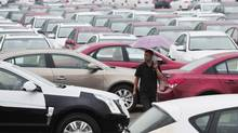 An employee walks past new cars at a General Motors parking lot in Shenyang, Liaoning province August 1, 2012. (SHENG LI/REUTERS)
