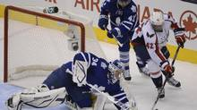 Toronto Maple Leaf goaltender James Reimer (34) reaches for the loose puck as Washington Capital right winger Joel Ward (42) also drives for it during an NHL game at the Air Canada Centre on Jan 31 2013. The Leafs earned a 3-2 win. (Fred Lum/The Globe and Mail)