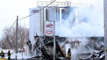 Firefighters hose down a fire at a cheese factory in St. Albert, Ontario east of Ottawa, Sunday, Feb. 3, 2013. A cheese factory east of Ottawa known for its poutine-topping curds has been gutted by a fire that broke out this morning. (FRED CHARTRAND/THE CANADIAN PRESS)