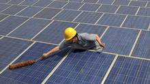A worker cleans solar panels on the rooftop of the Yiwu International Trade City in Yiwu, Zhejiang province in this file photo. (REUTERS)