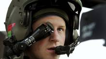 Prince Harry wears his monocle gun sight as he sits in his Apache helicopter in Camp Bastion, southern Afghanistan, in this photograph taken Dec. 12, 2012, and released Jan. 21, 2013. (POOL/REUTERS)