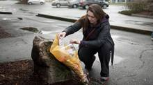 Heather Vince, a family friend of Julie Paskall, places flowers at a growing memorial at the Newton Arena and Community Centre in Surrey on Dec. 31, 2013. Ms. Paskall, 53, died Tuesday after being found beaten and unconscious on Sunday night. (RAFAL GERSZAK FOR THE GLOBE AND MAIL)