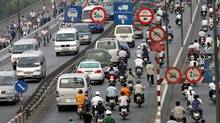 Cars and motorcyclists ride on the newly built bridge in Ho Chi Minh City, 24 April 2005.