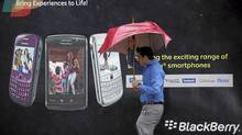 A man tries to hold on to his umbrella as he walks past a Blackberry advertisement billboard in Mumbai. (Danis Siddiqui/Reuters/Danis Siddiqui/Reuters)
