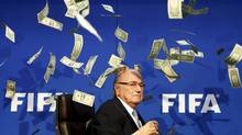 British comedian known as Lee Nelson (unseen) throws banknotes at FIFA's then-president Sepp Blatter as he arrives for a news conference in Zurich, Switzerland on July 20, 2015. FIFA finally revealed Blatter's pay deal on Thursday, which was $3.76-million (U.S.) in 2015 as soccer's embattled governing body reported a loss of $122-million for a year marred by scandal. (ARND WIEGMANN/REUTERS)