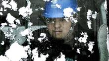 A worker looks through a snow-covered bus window while on his way to inspect electric power transmission lines after heavy snow in Huaibei Dec. 29, 2012. Temperatures in China, the world's top energy consumer, have hit 28-year lows this winter. (AP)